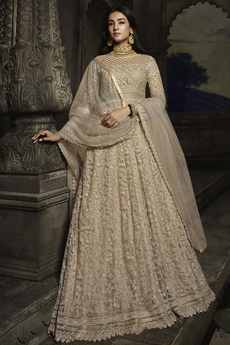 Sonal Chauhan Chikoo Color Function Wear Embroidered Floor Length Anarkali Dress In Net Fabric